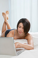 Young woman using laptop lying on bed