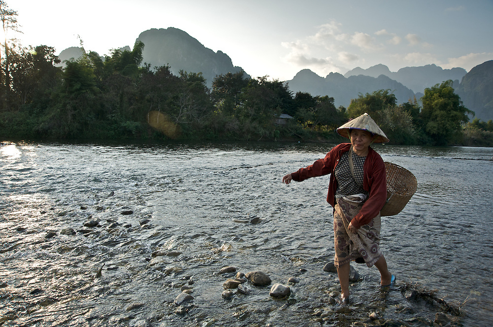 A woman crosses the Nam Song River near Vang Vieng, Laos after a day of working in the fields.