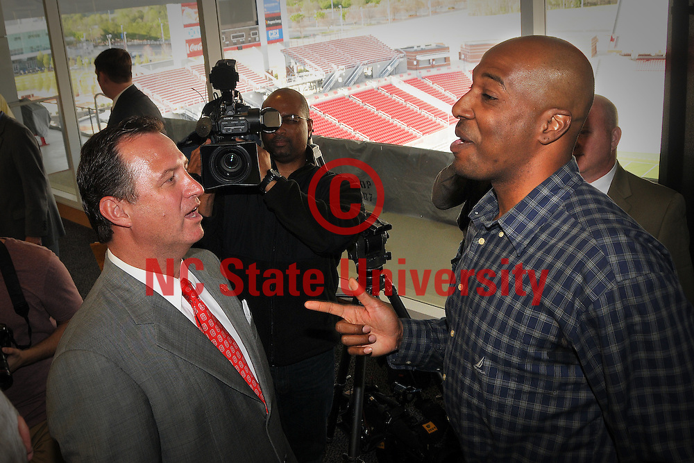 Mark Gottfried (left) chats with former Wolfpack standout Chucky Brown following the press conference announcing Gottfried as the new NC State men's basketball coach.