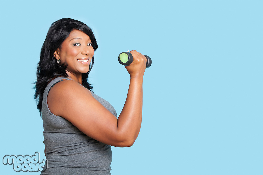 Portrait of mixed race woman lifting weights over blue background