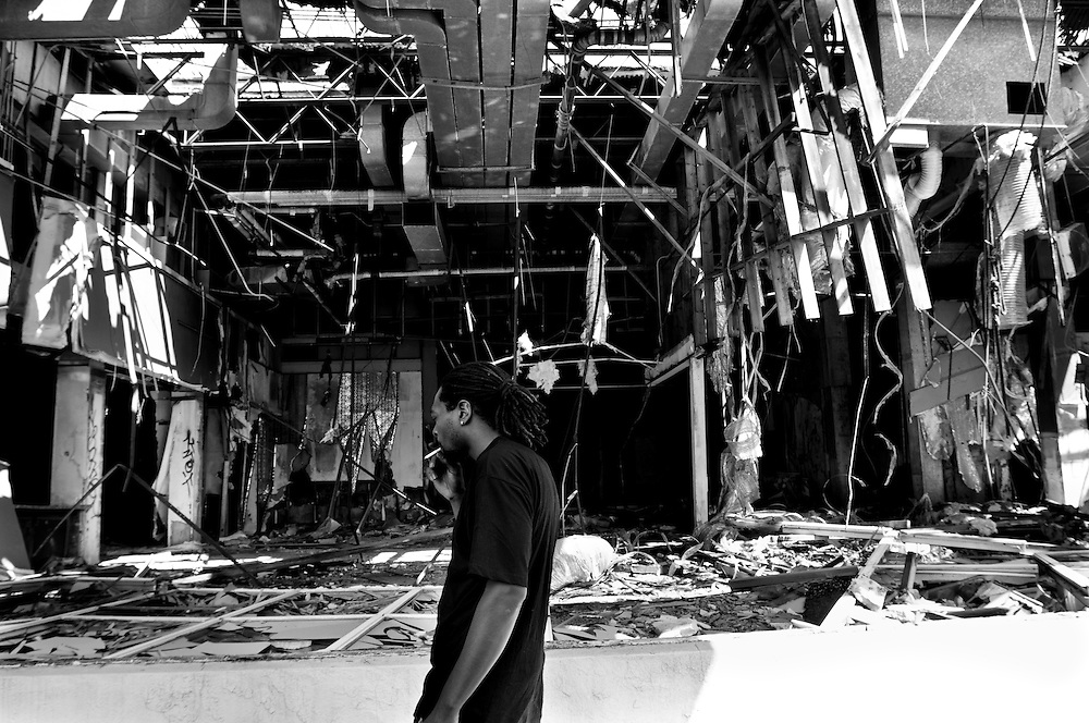 Ryan walks past a collapsing building in downtown Gary, Indiana. Gary's population peaked in the early 1960s at roughly 174,000 residents but has fallen to around 80,000 according to the latest U.S. Census in 2010. In addition to the collapsing infrastructure and deteriorating buildings, the number of abandoned houses is sharply increasing as people leave the city. (© William B. Plowman/Redux)