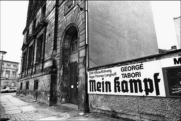 Duitsland, Oost Berlijn, 1-7-1990Op 1 juli 1990 werd de duitse monetaire eenwording effectief. De burgers van de ddr konden hun marken, ostmarken, inwisselen tegen de west-duitse mark, in winkels vond een grote operatie plaats om prijzen aan te passen en westerse producten in de schappen te leggen. Affiche van een theatervoorstelling Mein Kampf van George Tabori. Het vooroorlogse pand ernaast is nooit opgeknapt na de tweede wereldoorlog, 2e, oorlog en heeft zichtbare kogelgaten en oorlogsschade.Foto: Flip Franssen/Hollandse Hoogte