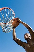 Basketball player slum dunking ball low angle view