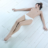 studio shot picture of a young beautiful breast naked  woman lying on a white floor