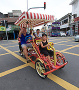 Malaysia, Penang. Old Georgetown Streets - a UNESCO World Heritage site. Tourists on four-wheeled bike.