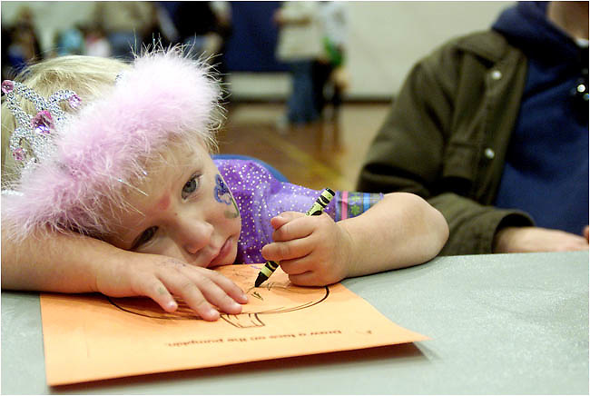 Allison Schmitt-Morris (2), of Coralville, ponders her next artistic crayon stroke as she colors in a pumpkin at the Coralville Rec Center after the Halloween parade Sunday Oct. 26, 2003 in Coralville. Over a hundred people turned out for the parade that started at S.T. Morrison Park and walked through the neighboring streets to finally end up at the rec center where there were games and prizes for the kids to enjoy.