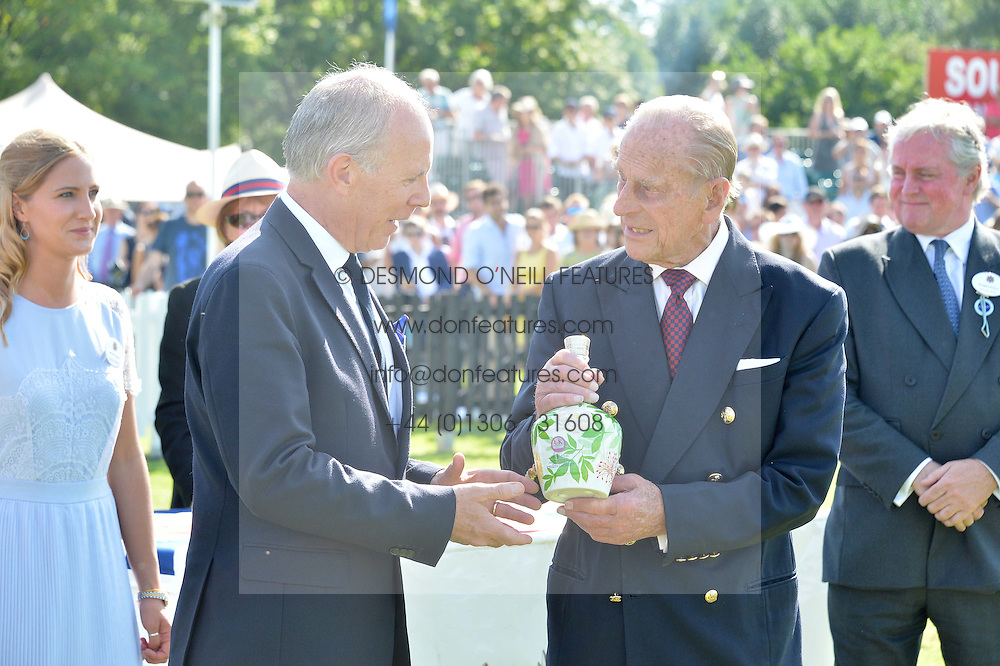 Left to right, PETER MOORE Global Prestige Brand Director of Royal Salute presents a bottle of rare whiskey to HRH The DUKE OF EDINBURGH at The Royal Salute Coronation Cup Polo held at Guards Polo Club,  Smiths Lawn, Windsor Great Park, Egham on 23rd July 2016.