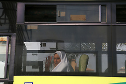 August 14, 2017 - Gaza, gaza strip, Palestine - A Palestinian woman is seen through a window en route to the Rafah border between the Gaza Strip and Egypt before leaving for the annual hajj pilgrimage to the holy city of Mecca, in Gaza City, early , Aug. 14, 2017. Hundreds of Palestinian pilgrims are leaving Gaza through the Rafah border crossing with Egypt on their way to Mecca, Saudi Arabia, for hajj. Egypt has agreed to keep the crossing open for three days to allow thousands of people to cross. (Credit Image: © Majdi Fathi/NurPhoto via ZUMA Press)