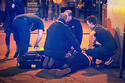 "© Licensed to London News Pictures . 19/12/2015 . Manchester , UK . Paramedics attend to a man lying on the pavement in the city's Northern Quarter . Revellers in Manchester enjoy "" Mad Friday "" - also known as "" Black Eye Friday "" - the day on which emergency services in Britain are typically at their busiest , as people head out for parties and drinks to celebrate Christmas . Photo credit : Joel Goodman/LNP"