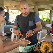 NOVEMBER 23 - TOA ALTA, PUERTO RICO - <br /> Angel Joel Alvarez, 34, serves Thanksgiving turkey  to his mother in law Nancy Ojeda, 62, in the Comunidad Las Acerolas. The house has been without power since Hurricane Maria and it's sheltering several family members. <br /> (Photo by Angel Valentin/FREELANCE)