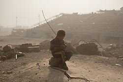 Licensed to London News Pictures. 08/11/2016. Qayyarah, Iraq. A young Iraqi boy plays with a toy mobile phone as he sits on a destroyed ISIS headquarters, located in a football stadium destroyed by an airstrike, where he and his friends are playing in the Iraqi town of Qayyarah, Iraq. Oil wells in and around the town of Qayyarah, Iraq, we set alight in July 2016 by Islamic State extremists as the Iraqi military began an offensive to liberated the town.<br /> <br /> For two months the residents of the town have lived under an almost constant smoke cloud, the only respite coming when the wind changes. Those in the town, despite having been freed from ISIS occupation, now live with little power, a water supply tainted with oil that only comes on periodically and an oppressive cloud of smoke that coats everything with thick soot. Many complain of respiratory problems, but the long term health implications for the men, women and children living in the town have yet to be seen. Photo credit: Matt Cetti-Roberts/LNP