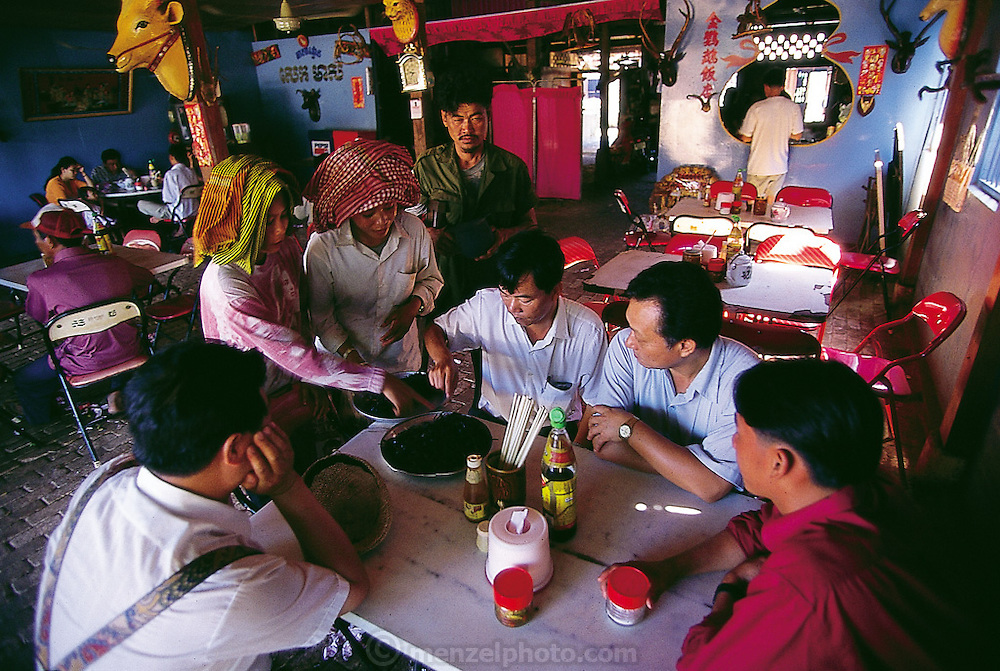 Cambodian men purchasing deep-fried tarantulas from tarantula seller Sok Khun in a roadside restaurant, not only for their taste, but also for their alleged benefits to a man's virility, Kâmpóng Cham Province, Cambodia. (Man Eating Bugs page 49) .