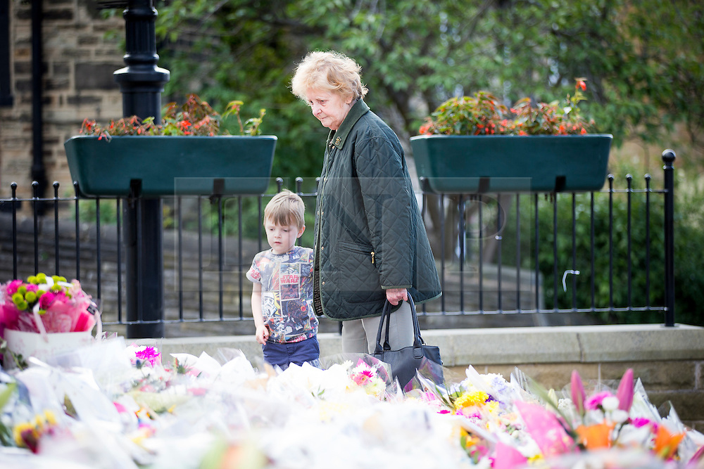 © Licensed to London News Pictures. 22/06/2016. Birstall UK. On what would have been MP Jo Cox's 42nd a lady & child look at the sea of flowers left in Birstall market square near the scene where MP Jo Cox was murdered last week. Photo credit: Andrew McCaren/LNP