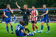 Referee John Busby awards a yellow card just outside the box to Sunderland Luke O'Nien during the EFL Sky Bet League 1 match between Rochdale and Sunderland at the Crown Oil Arena, Rochdale, England on 20 August 2019.