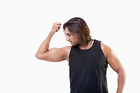 Young Asian man flexing muscles over white background