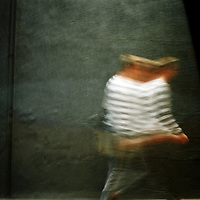Figure walking in street with blurred action