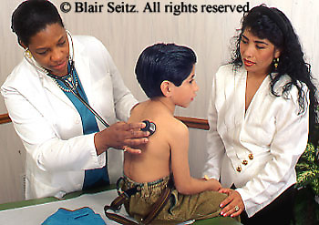 African American Doctor, Hispanic Boy Examination, Physician at Work, Hispanic Mother Watches, Urban Clinic