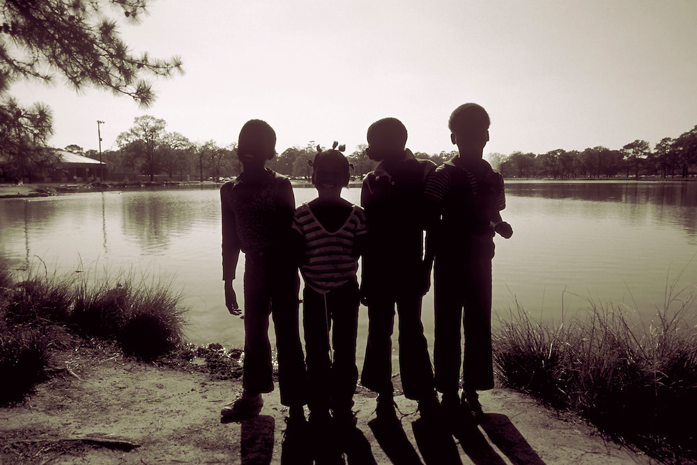Silhouette of four kids having summer fun with friends posing for a picture at Herman Park Lake, Houston, Texas.