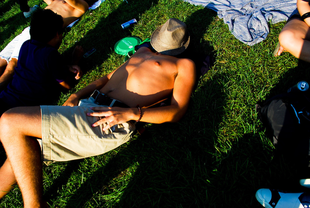 A man naps under his hat in the grass at the JELLY Pool Party free concert series at East River State Park, Brooklyn, New York, 2009