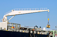 Crane loading supplies on deck of ship
