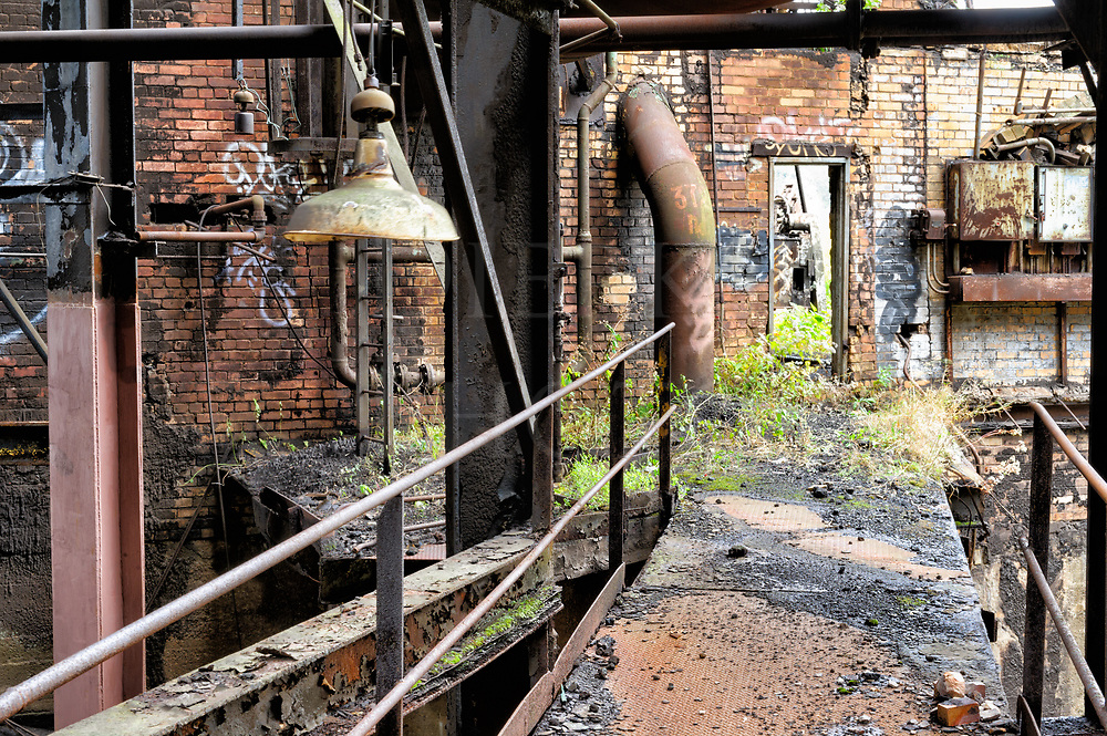 A walkway through an abandoned industrial scene, a very chaotic scene of desolation at Carrie Furnace which was part of the steel mill complex near Braddock outside of Pittsburgh PA.