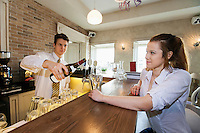 Bartender pouring wine for female customer at restaurant counter
