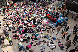 © Licensed to London News Pictures. 01/06/2019. Bristol, UK. Extinction Rebellion protest in Bristol's Cabot Circus shopping centre against fast fashion and consumerism. Campaigners from Extinction Rebellion are carrying out a five-hour protest which will include everything from a 'pop-up' catwalk to blocking the city centre traffic. The protest targets Bristol's fashion and clothes stores with people urged to not buy any new items of clothing for the next year. There will also be a 'pop-up catwalk', where designers will be showing off their work to demonstrate the needed shift away from fast fashion towards a fairer, safer, cleaner, more transparent fashion industry. People are encouraged to repair, re-use, alter, upcycle and recycle clothes in a year-long boycott aiming to economically disrupt the fashion and textile industry demanding that it drastically changes the way it currently exploits people and planet for profit. The protest is part of a series of disruptive activities planned by Extinction Rebellion to highlight the fashion industry's contribution to climate change, biodiversity loss and environmental pollution. Photo credit: Simon Chapman/LNP.