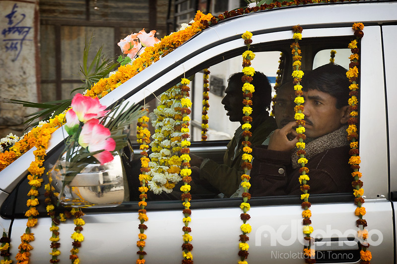Men going to a wedding have ornated their car with traditional flower lines. Rajasthan, India
