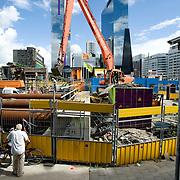"""Nederland Rotterdam 3 september 2007 20070903 .Voorbijgangers bekijkt de werkzaamheden in de enorme bouwput voor het centraal station Rotterdam.   ."""" Het doek is gevallen """" Zondag 2 september is het doek letterlijk doek gevallen voor het in 1957 geopende gebouw. Over enkele weken wordt de schepping van architect Sybold van Ravesteyn gesloopt en komt op het Stationsplein een nieuwe OV-terminal, die na 2011 ruim 300.000 reizigers per dag moet kunnen verwerken. Voorbijgangers maken een foto van het oude bekende centraal station, dat sinds 1957 dienst heeft gedaan. Een gloednieuw station zal op deze plek verrijzen. ..Het tijdelijke station dat de periode overbrugt tussen de sloop van het oude Rotterdam CS en de bouw van een nieuw station, kost 12 miljoen euro. Dat is een schijntje vergeleken met het half miljard waarop het nieuwe is begroot. De bedoeling is dat de tijdelijke bebouwing in februari klaar is. Het blijft open tot 2010. Het oude gebouw maakt plaats voor vijf tijdelijke. Daarvan zijn er vier voor de reizigers en een voor het personeel van de Spoorwegpolitie. ..Tijdelijk Rotterdam Centraal.1 september 2007..Alle treinreizigers opgelet! Vanaf 2 september sta je voor een dichte deur als je bij Rotterdam Centraal op de trein wilt stappen. Tenzij je de ingang van het tijdelijke Rotterdam Centraal al gevonden hebt. ..Naast het oude vertrouwde station staat al een tijdje een groot blauw gebouw en vanaf 2 september kun je daar op je trein stappen. Je kunt er zelfs een kopje koffie halen, of kleine boodschappen doen. Alle winkels zijn namelijk gewoon verplaatst naar het grootste tijdelijke station van Nederland...Het Centraal Station was al een hele tijd een grote bouwput, want er wordt heel hard gewerkt aan een nieuw, beter en vooral moderner station. Maar omdat afscheid nemen altijd zo moeilijk is, vindt er op 12 september een soort ode aan het station en de architect Sybold van Ravesteyn plaats. De letters Centraal Station worden omgetoverd tot Traan laten. De lett"""