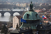 Westward views from Letna Park to the district of Hradcany and the Charles Bridge on the Vltava river where the EU and Czech flags fly over a government building, on 18th March, 2018, in Prague, the Czech Republic. Like Rome, Prague is built on seven hills.