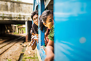 15 JUNE 2013 - YANGON, MYANMAR:  Passengers look out the window of the Yangon Circular train as it goes around Yangon. The Yangon Circular Railway is the local commuter rail network that serves the Yangon metropolitan area. Operated by Myanmar Railways, the 45.9-kilometre (28.5mi) 39-station loop system connects satellite towns and suburban areas to the city. The railway has about 200 coaches, runs 20 times and sells 100,000 to 150,000 tickets daily. The loop, which takes about three hours to complete, is a popular for tourists to see a cross section of life in Yangon. The trains from 3:45 am to 10:15 pm daily. The cost of a ticket for a distance of 15 miles is ten kyats (~nine US cents), and that for over 15 miles is twenty kyats (~18 US cents). Foreigners pay 1 USD (Kyat not accepted), regardless of the length of the journey.     PHOTO BY JACK KURTZ