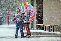 Ashley Jennings, 9, comes out from under the shelter of her colorful umbrella to catch snowflakes on her tongue Tuesday while at recess with her friend Tyhler Fulkerson, 8, at Atlas Elementary in Hayden.