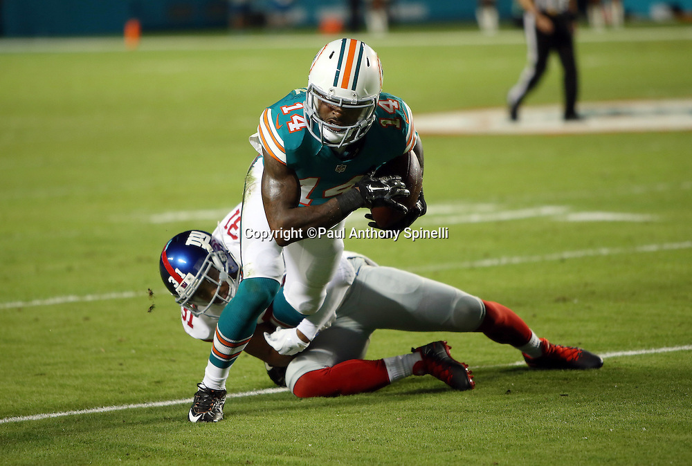 Miami Dolphins wide receiver Jarvis Landry (14) gets tackled by New York Giants defensive back Trevin Wade (31) after catching a first quarter pass short of a first down on a third down play during the NFL week 14 regular season football game against the New York Giants on Monday, Dec. 14, 2015 in Miami Gardens, Fla. The Giants won the game 31-24. (©Paul Anthony Spinelli)