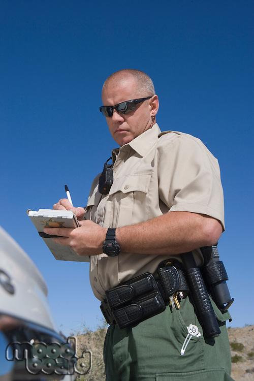 Policeman writing speeding ticket