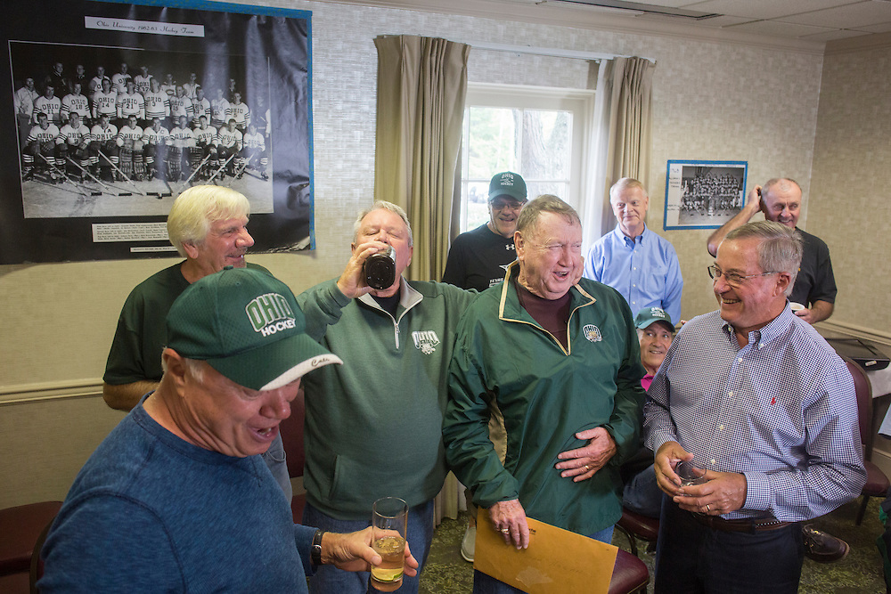 Bing Carlson takes a drink from a bottle of Purple Cow Cocktail while other hockey alumni watch during the 1960s hockey alumni reunion at the OU Inn on October 1, 2016.