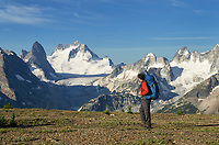 Adult male backpacker admiring view on Rocky Point Ridge. Howser Towers, Vowell Glacier, and Northern Bugaboos in the distance. Bugaboo Provincial Park Purcell Mountains British Columbia.