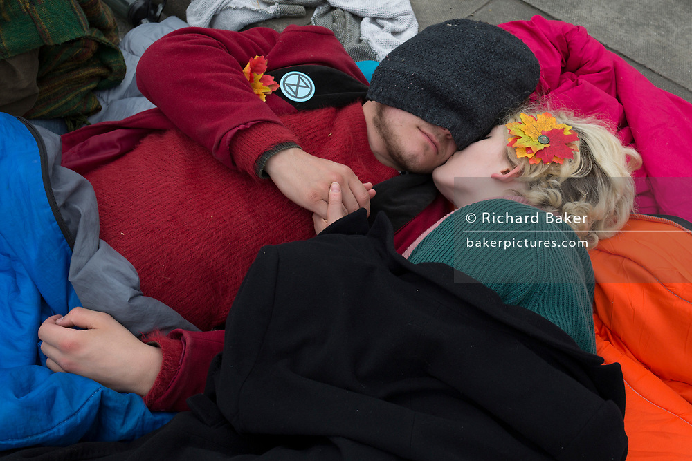 Two Climate Change activists with Extinction Rebellion rest while campaigning for a better future for planet Earth after blocking Waterloo Bridge and as part of a multi-location 5-day Easter protest around the capital, on 16th April 2019, in London, England.