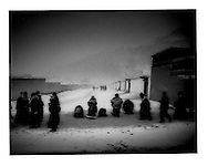 """Arjopa"" Tibetan pilgrims stop during circumambulation of Labrang Monastery to prostrate in the direction of the main prayer hall, Labrang, Amdo, Tibet (Xiahe, Gansu, China)."