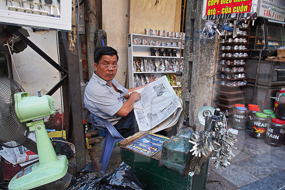 A key maker reads a newspapers in a street of Hanoi's Old Quarter, Vietnam, Southeast Asia, 2016