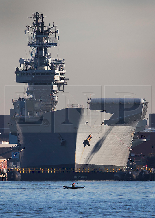 © Licensed to London News Pictures. 30/11/2016. Portsmouth, UK. A lone canoeist passes in front of the former Royal Navy aircraft carrier HMS Illustrious in dock, before she is moved out into the harbour ahead of her final voyage to a scrap yard.  The last of the Invincible Class carriers has been sold to the Leyal Ship Recycling and Dismantling company in Aliaga, Turkey - the same yard that dismanled Illustrious' sister ships Ark Royal and Invincible. Photo credit: Peter Macdiarmid/LNP