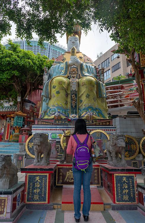 Girl worships Tin Hau Statue (Goddness of the Sea) in Tin Hau Temple, Repulse Bay, Hong Kong Island, China