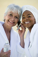 Portrait of two women in bathrobes using mobile phone
