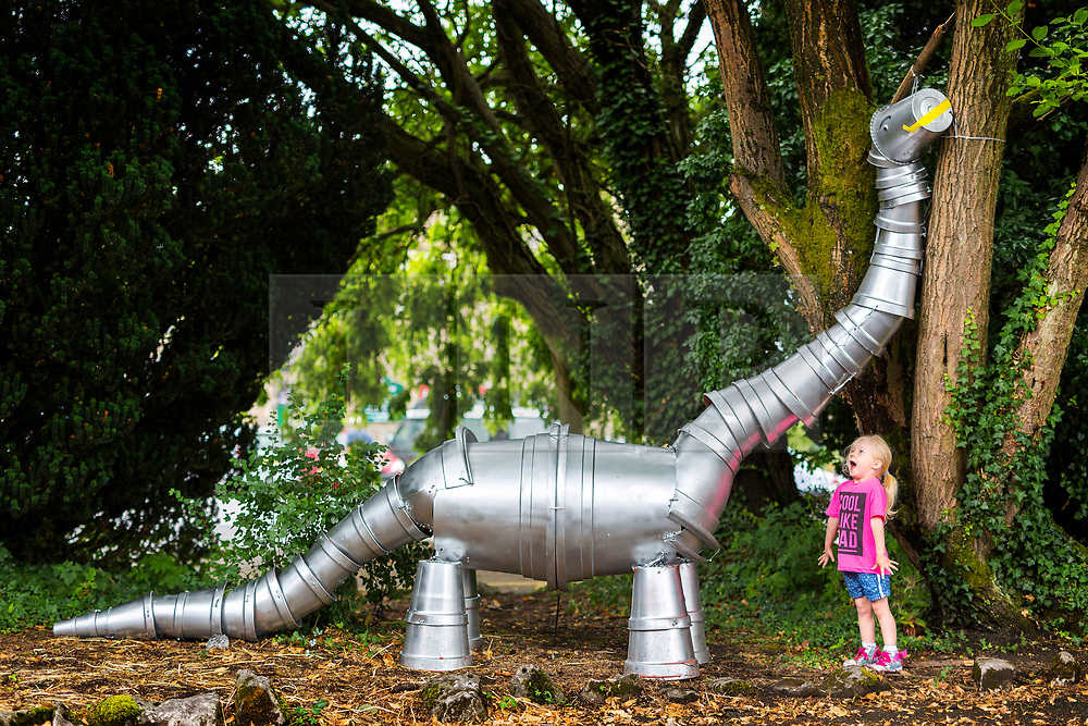 © Licensed to London News Pictures. 17/07/2018. Settle UK. A little girl looks at a Dinosaur made entirely of flowerpot's in the market town of Settle in the Yorkshire Dales. The Settle flowerpot festival runs through July & August & see's 100's of flowerpot creations placed around the town. Photo credit: Andrew McCaren/LNP