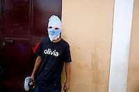 A men wearing a mask and holding a Molotov cocktail stands in front of the mayors office Tuesday Sept. 11, 2007, Palin Guatemala. A angry mob took to the streets and went on to burn down the mayors office as well as his home in demonstration after and clash with local police on the previous day. Residents accuse the mayor of, among other things, of bussing voters for the elections on Sept. 9 2007.   (photo by/ Darren Hauck)...........