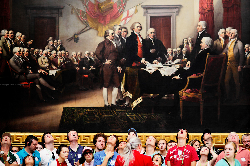 """Tourists are gazing up on the ceiling in the rotunda in the US Congress, with the painting of """"The Founding Fathers"""" as their backdrop."""
