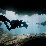 Videographer swimming out of an underwater cave near Mexico Rock, Ambergris Caye, Belize