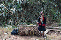 A tribal woman waits for a bus with her crops in Northern Laos