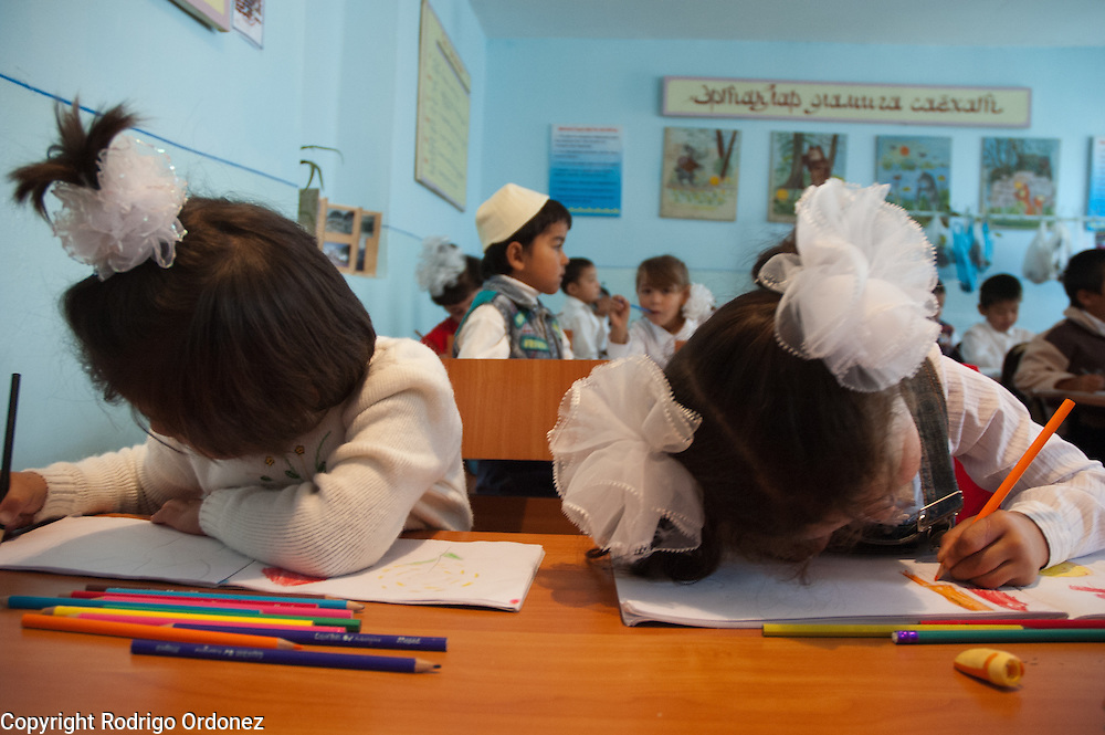 Two girls draw a picture at School 110 Boston, in Osh (Kyrgyzstan), where Save the Children supports a child-friendly space.