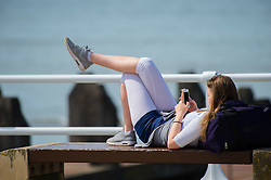 © London News Pictures. 05/05/2016. Aberystwyth, UK. A young woman relaxing with her smart phone,  enjoying the warm spring sunshine in Aberystwyth Wales. The temperature is forecast to rise over the coming days,  as a plume of warm air moves in from the near continent,  reaching the low 20's centigrade by the weekend. Photo credit: Keith Morris/LNP