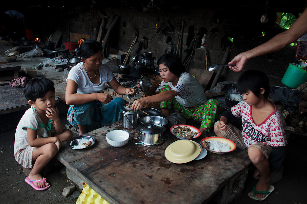 Nmau Hkawn Htoija, 14, from Shadanpa village, take the breakfast with her sisters Kai Seng, left, and Jinu Mai, right and her mother Hpanyam Roi Ji, 2nd left, in the common kitchen of Woi Chyai Internal Displacement People refugee camp in Laiza village close to the China border, Myanmar on July 16, 2012. According to KIO (Kachin Independence Organization) sources around 50000 Kachin people live as refugees in those camps.